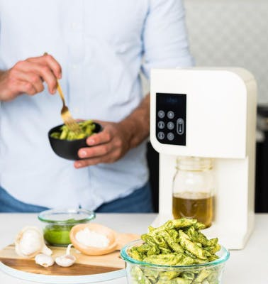 LEVO weed machine and cannabutter maker sits on a counter as someone prepares infused pesto pasta.