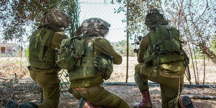 Three military members in a field.