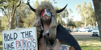A man at a protest wearing horns, he is known as the QAnon Shaman.