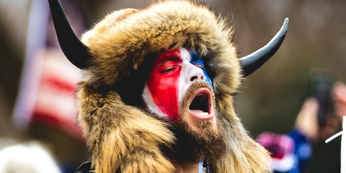 """Jake Angeli, the """"Qanon Shaman"""" in red white and blue face paint and headdress."""