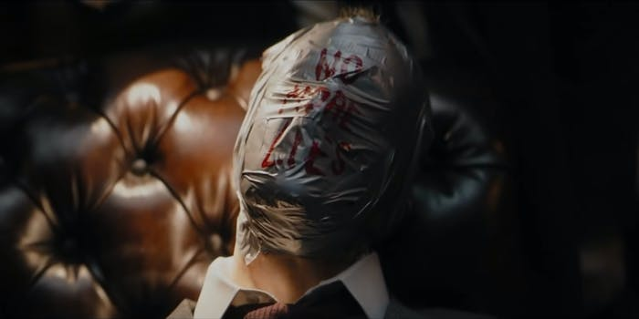 """man in chair with head covered in duct tape, """"no more lies"""" written in red on the tape"""