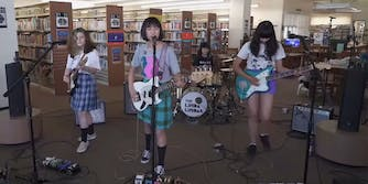 Four young girls perform on bass, guitars, and drums in a public library.