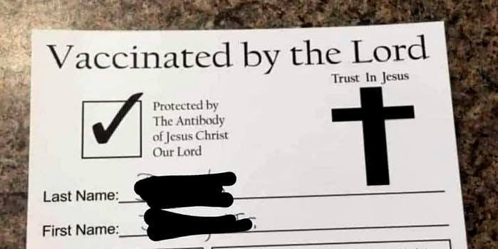 A piece of paper that says 'Vaccinated by the Lord.'