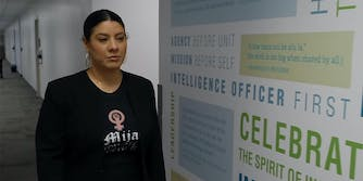 """woman in """"Mija you are worth it"""" t-shirt walks past CIA wall art that reads """"Agency before unit, Mission before self, Intelligence officer first"""""""