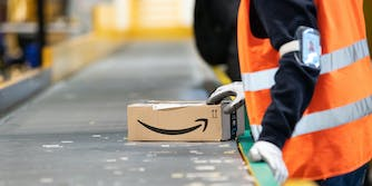 An Amazon warehouse worker pushing a package down a conveyer belt.