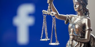A statue of a woman holding a scale, representing the justice system. Behind the statue is a blurred out Facebook logo.