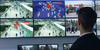An official looking at numerous computer screens that are using facial recognition technology.