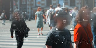 People walking on a street. Their faces are blurred and facial recognition technology is being used on them.