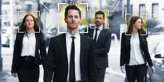 Four people walking down the street having their face scanned with facial recognition.
