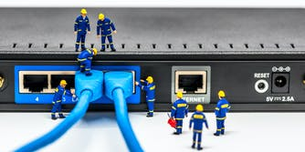 Group of engineer figurines connecting broadband fiber network cables to a router. It is meant to convey closing the digital divide through infrastructure investment.