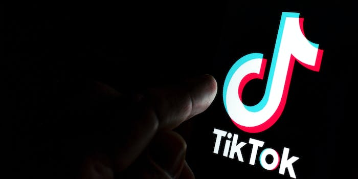 TikTok app logo on screen and a finger pointing at it.