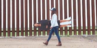 Lauren Boebert walking in front of border fence with cardboard cutout of Kamala Harris