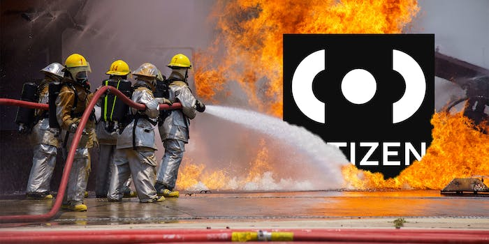 Firefighters hosing down the Citizen app logo, which is engulfed in flames