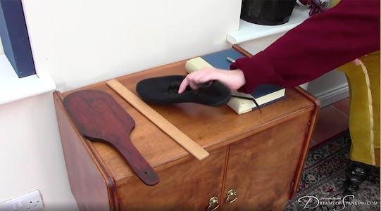 Pandora Blake grabs a black sneaker off of a dresser.