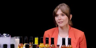 woman sitting in front of hot sauce bottles