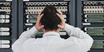 man in network server room with hands on head