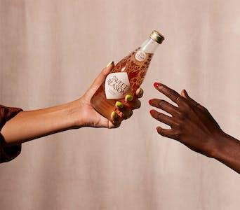 someone hands someone else a bottle of sweet reason hemp cbd infused drinks