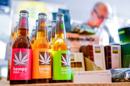 Hemp-based drinks sit in beer style bottles on a store counter with other items for sale in the background which is out of focus