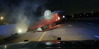 car crashed upside down on highway from perspective of a police cruiser