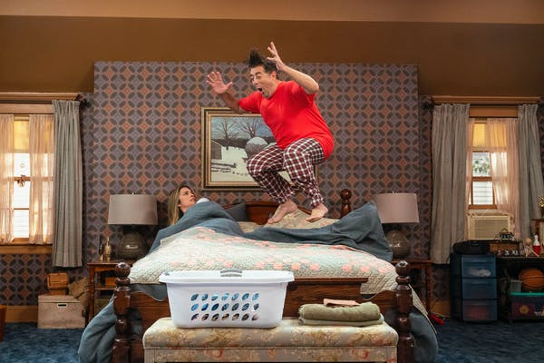 woman lays in bed while man is mid-jump