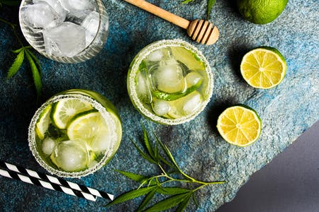 Liquid cannabis in the form of marijuana drinks on a stone table surrounded by weed leaves and limes