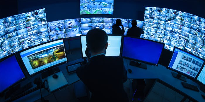 A CCTV security room looking at monitors, the cameras show facial recognition being used.