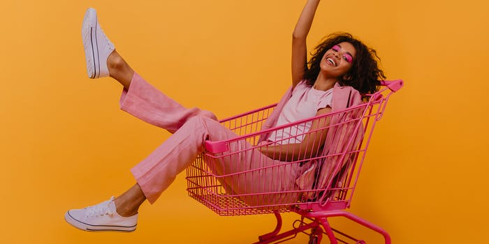 Young woman in shopping cart, smiling