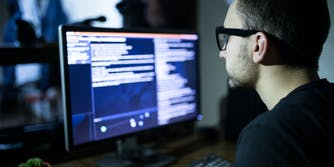 A person at a computer carrying out a cyber attack in the dark.