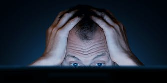 A man with his hands on his head looking frustrated in front of a computer.