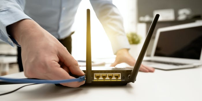 Man connects the internet cable to the router's socket. Fast and wireless broadband internet concept.