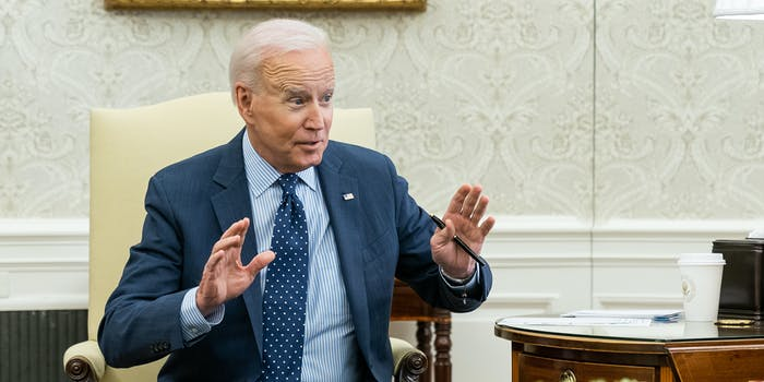 President Joe Biden holding up his arms while sitting in the Oval Office.
