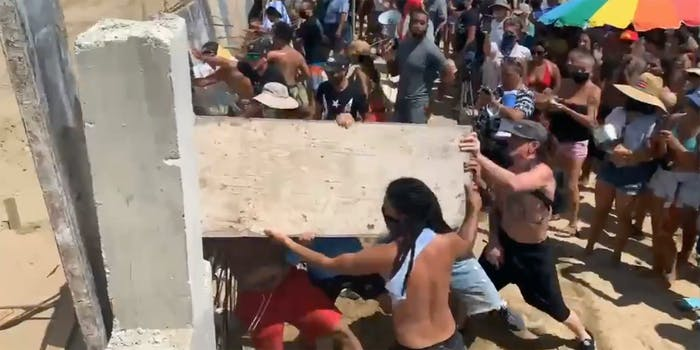 People busting down a fence.