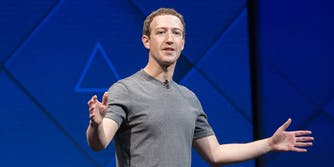Facebook CEO Mark Zuckerberg giving a speech on a stage with his arms stretched out.