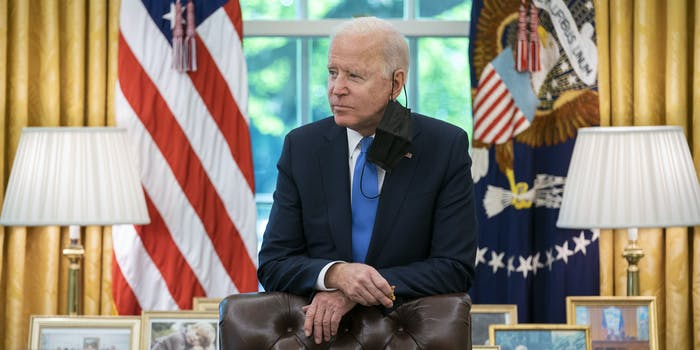 President Joe Biden looking off to the right inside the Oval Office.