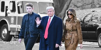Donald Trump waves as he walks with First Lady Melania Trump and their son Barron