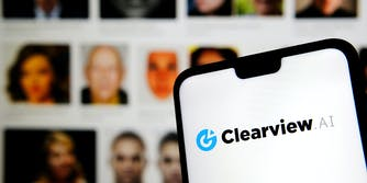 A phone showing the Clearview AI logo on it. Behind it is a series of people's photos.