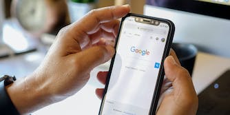 A person holding a smartphone with the Google homepage on it.