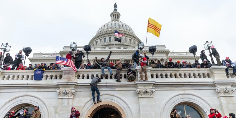A photo from the January 6 capitol riot showing Trump supporters climbing the Capitol.
