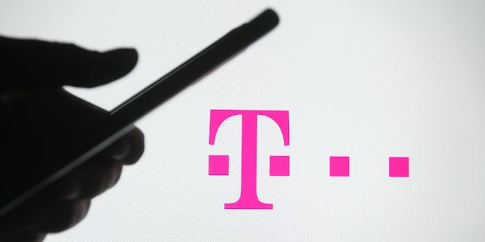 A person holding a smartphone in front of the T-Mobile logo.