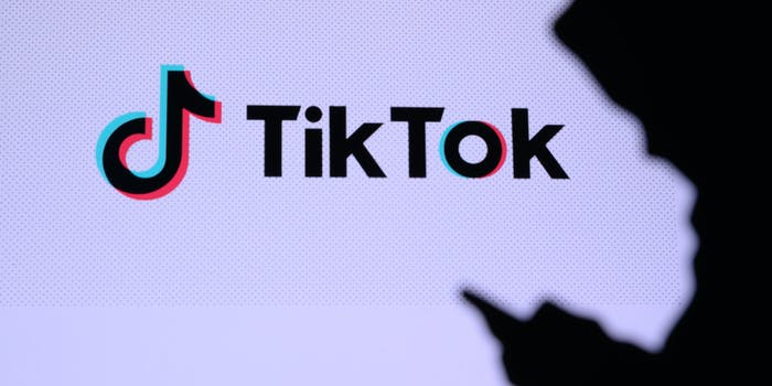 A person in shadows using a phone. Behind them is the TikTok logo.