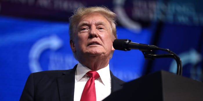 Former President Donald Trump speaking in front of a microphone.