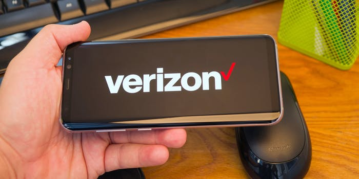 A person holds a smartphone with the Verizon logo on it.