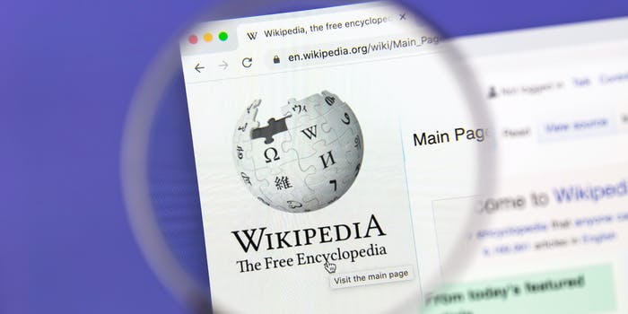 The logo of Wikipedia on a webpage behind a magnifying glass.