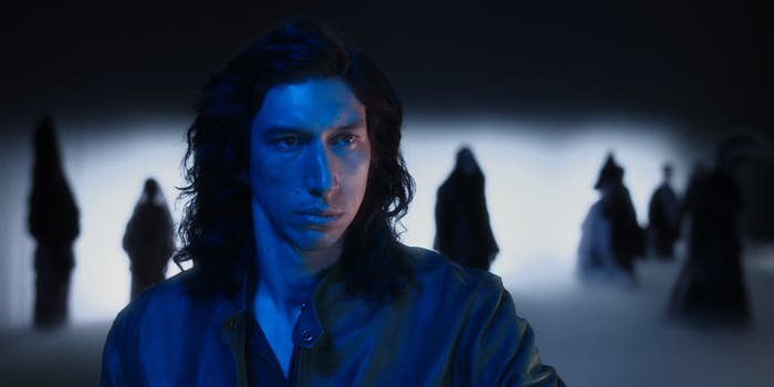 man staring ahead and standing in blue light