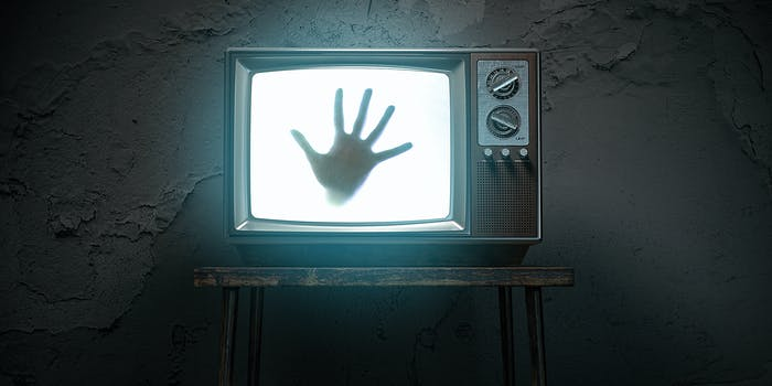 A hand coming out of a television.