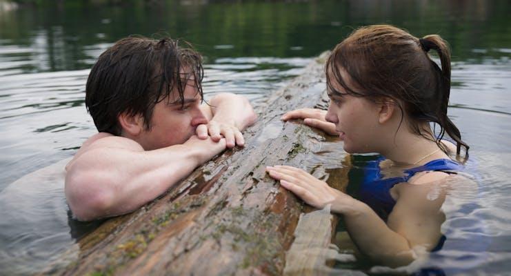 two teens look across the log