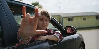 teen girl making i love you sign in car