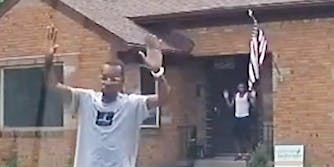 Two black men with their hands in the air.