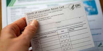 hand holding COVID-19 vaccination card