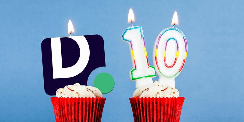 Daily Dot logo candle and Number 10 birthday candle in cupcakes against a blue background